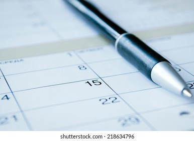 Ballpoint pen lying on a calendar with selective focus to the date of the 15th, calendar at an oblique angle