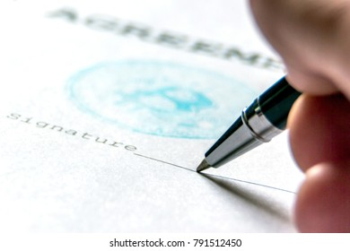 A ballpoint pen in the person's hand on a piece of paper with a bitcoin stamp puts a signature. Macro. The concept of the contract of purchase for bit-coin.