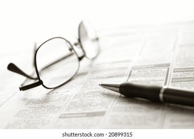 Ballpoint pen and reading glasses on newspaper jobs and help wanted employment classifieds ads section for an unemployment recovery job search