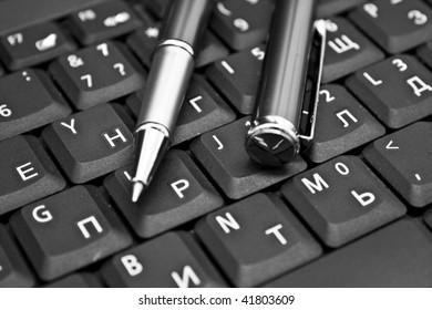 Ballpoint pen resting on computer keyboard. Blue tone, focus on pen tip.