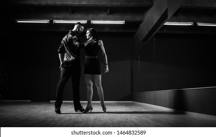 Ballroom dancers. The guy with the girl is engaged in ballroom dancing. Ballroom dancing. Dancing. The guy with the girl dancing in a dark room. Black and white.