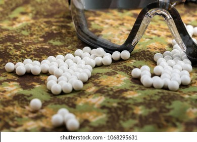 balls airsoft bbs and protective glasses on a camouflage background