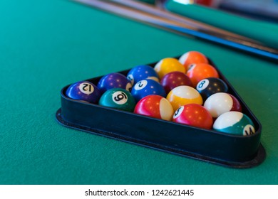 Balls for billiards pool snooker are on green table.
