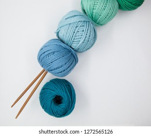 balls of blue and green wool and white background