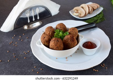 Balls with buckwheat and mushrooms in a white bowl on a grey abstract background. Dieting. Fasting food. healthy eating concept