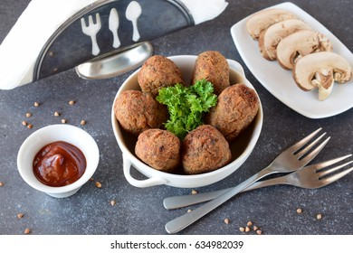 Balls with buckwheat and mushrooms in a white bowl on a grey abstract background. Dieting. Fasting food. Step by step cooking