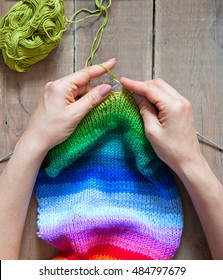 Balls of colored yarn. View from above. All the colors of the rainbow. Sample knit. Women's hands are knitted.
