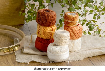 Balls of cotton threads in orange and beige color are on the wooden table with flower background