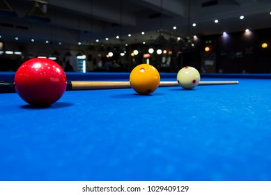 Balls and a cue seen on the table of a Carom Billiard.