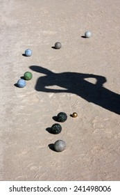 Balls and man shadow on the ground of bocce ball court