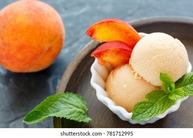 Balls peach ice cream and mint leaves in bowl on wooden plate, selective focus.