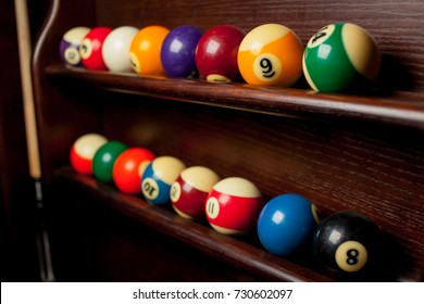 Balls for pool billiards on the shelf / billiard balls for American billiards / balls for Russian billiards / colored or white balls for billiards on a wooden background. Close-up photo. Soft focus.