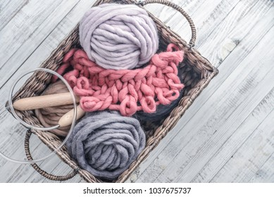 Balls of  super chunky merino woolen yarn with needles in rustic  basket on light blue background.