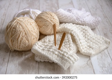 balls of white yarn and knitting needles