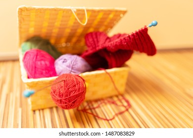 Balls of wool in a basket for needlework. Knitting warm and cozy things.