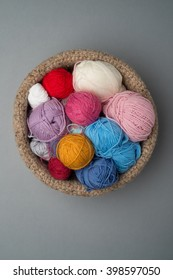 Balls of wool of different colours in a crocheted bowl on a grey background.