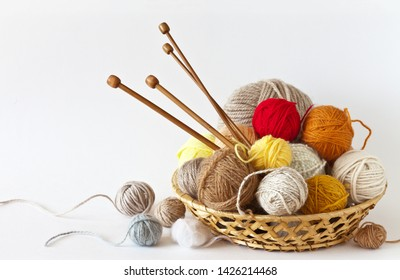 Сolorful balls of wool yarn and knitting wooden needles in a wicker basket on a white background. Still life, place for text, closeup