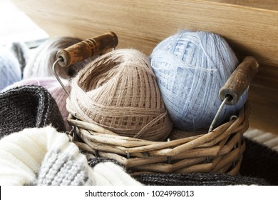 Balls of wool yarn in a wicker basket. Threads for needlework.