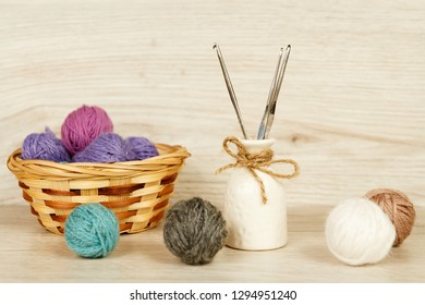 Balls of yarn for knitting on a light wooden background. Decorations for Valentine's Day and Mother's Day. Romantic atmosphere.