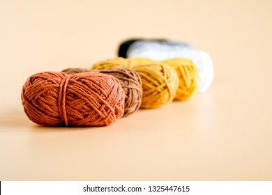Balls of yarn or wool on orange background , wool is the textile fiber obtained from sheep and other animals. Object textile for knitting and crochet as clothes, dolls. Hobby and handmade concept.