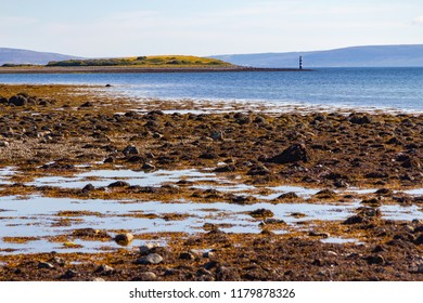 Ballyloughane Beach with lighhouse and Hare Island, Galway, Ireland