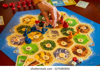 Balogunyom / Hungary - 01.04.2019: Board game party Settlers of Catan, popular board game. Players are scrambling the area to get more resources and victory points.