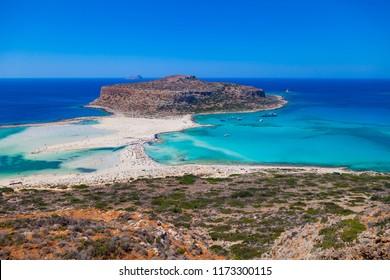Balos lagoon (Balos beach) on Crete island. Tourists relax and bath in crystal clear water of Mediterranean Sea, Greece.