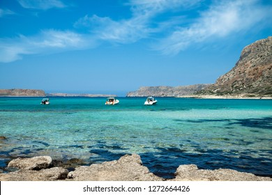 Balos lagoon on Crete island in Greece. Tourists relax and bath in crystal clear water of Balos beach.
