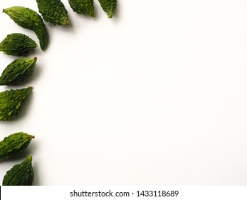 Balsam apple, Balsam pear, Bitter cucumber, Bitter gourd, Bitter melon, Carilla fruit on white background, Top view with copy space.