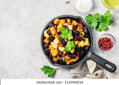 Balsamic roasted vegetables, carrots, sweet potato, pumpkin, beetroot, potato in cast iron skillet. Top view, space for text.