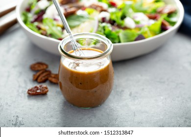 Balsamic vinaigrette dressing for a salad, small glass jar with a whisk