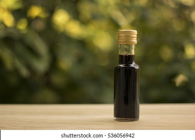 Balsamic vinegar bottle on the table in garden. Wine vinegar. Healthy eating concept. Mediterranean cuisine.