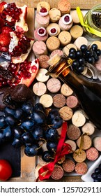 balsamic vinegar in a glass jug with fresh red grapes on wine corks, food rich with resveratrol, flavonoids, antioxidants, pomegranate, cranberry, blueberry, tomatoes