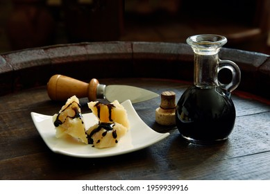 Balsamic Vinegar of Modena with Parmesan flakes set on plates and a wooden barrel