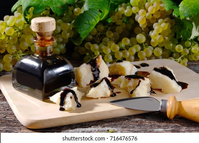 Balsamic vinegar of Modena with pieces of Parmesan cheese and grapes in the background