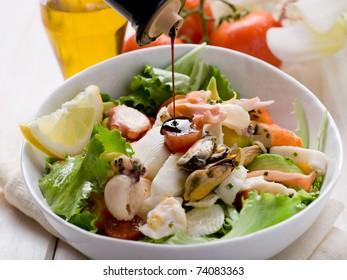 balsamic vinegar over mixed seafood salad with mozzarella and avocado