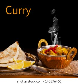 Balti dish with chicken curry with visible steam rising, served with naan bread and lemon, on a black background with space for text. Front to back focus.