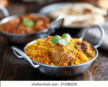 balti dish with indian chicken biryani and curry in the background