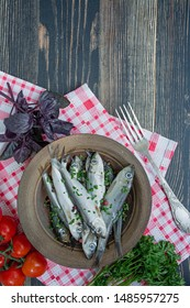 Baltic herring seafood. Salted herring fish in a bowl with spices and herbs. Wood background.