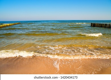 Baltic Sea with groins and surf and blie sky