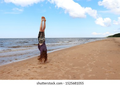 Baltic Sea, Latvia - July 17, 2019: Teenage girl (14) doing a handstand on a sandy beach at the Baltic Sea in Latvia on a summer day.