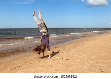 Baltic Sea, Latvia - July 17, 2019: Teenage girl (14) doing a handstand on a sandy Baltic Sea beach in Latvia  on a warm summer day.