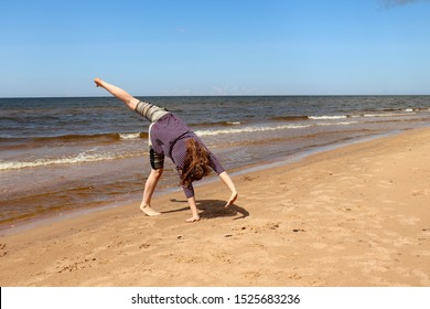 Baltic Sea, Latvia - July 17, 2019: Teenage girl (14) doing a cartwheel on a sandy beach at the Baltic Sea in Latvia on a warm summer day in July.
