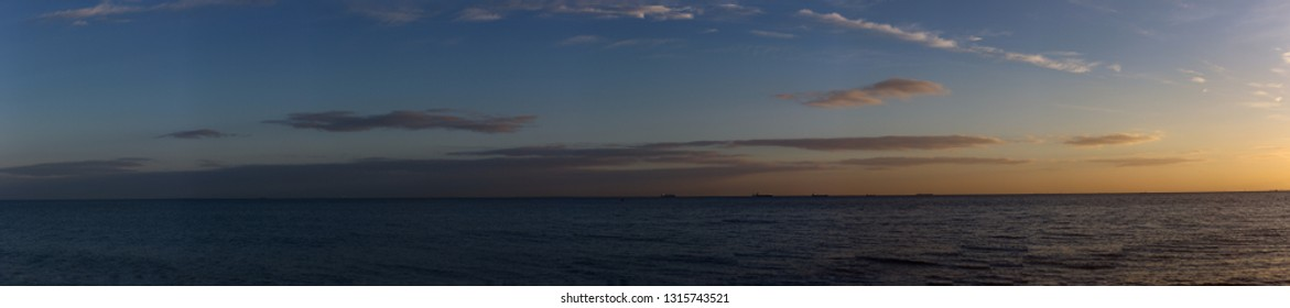 Baltic sea panorama at 6 am in the golden hour period. Wide seascape view of the sea with deep shadows and colored sky.