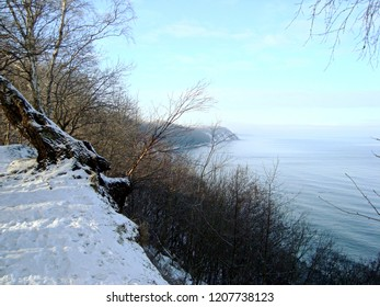 Baltic sea shore in winter. Steep descent to water against blue sky. Steep river bank. Sunny wintry landscape.