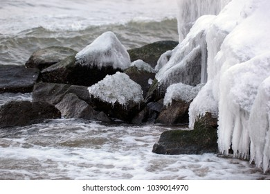 Baltic sea side landscape in winter -  detail of wave breaker   in Poland - icicles and white snow on old huge brown stones  with water and waves on a sandy beach  with natural sunlight