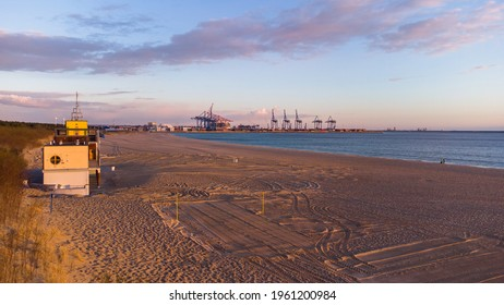 Baltic Sea and the Stogi beach in sunrise colors with DCT terminal, Gdansk. Poland.