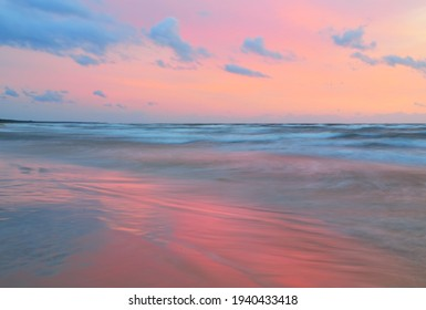 Baltic sea at sunset. Dramatic sky, blue and pink glowing clouds, soft golden sunlight. Waves, splashing water. Picturesque dreamlike seascape, cloudscape, nature. Panoramic view, long exposure - Shutterstock ID 1940433418