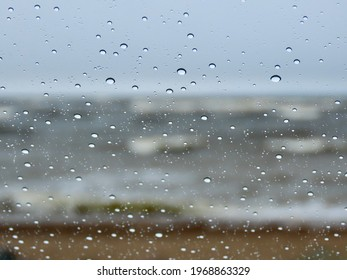 Baltic sea waves during a spring storm seen through a window with raindrops close up and bokeh blurry grey blue sea, huge white waves in far background