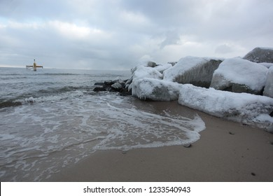 baltic sea wide angle winter landscape with a snowy beach with huge brown frozen rocks wave breaker with ice and icicles, outdoors in Gdańsk, Europe, Poland